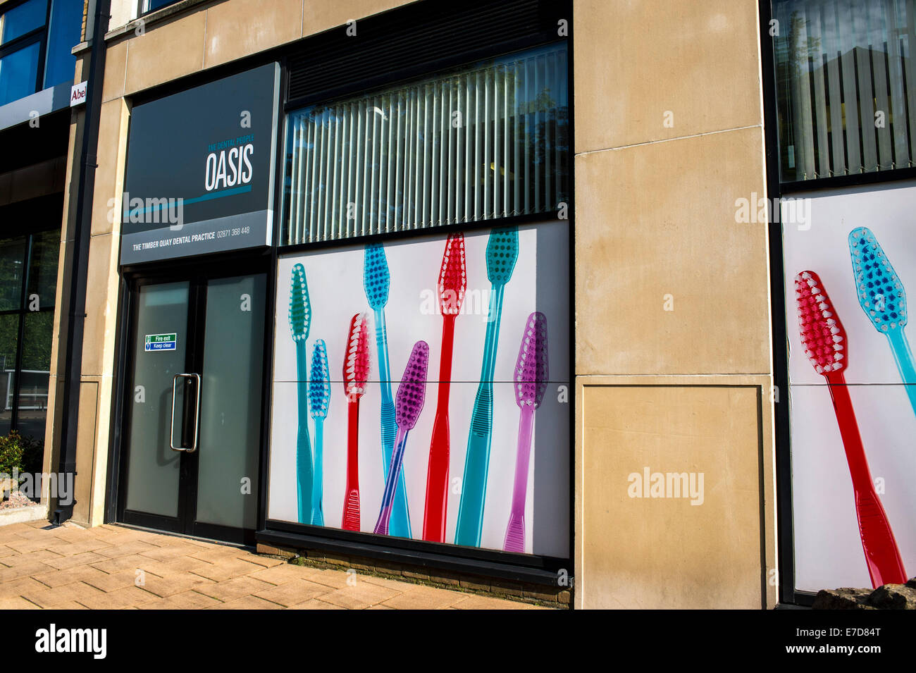 Large illustration of coloured tooth brushes on exterior of dentistry pracrice, Derry, Londonderry, Northern Ireland. - Stock Image