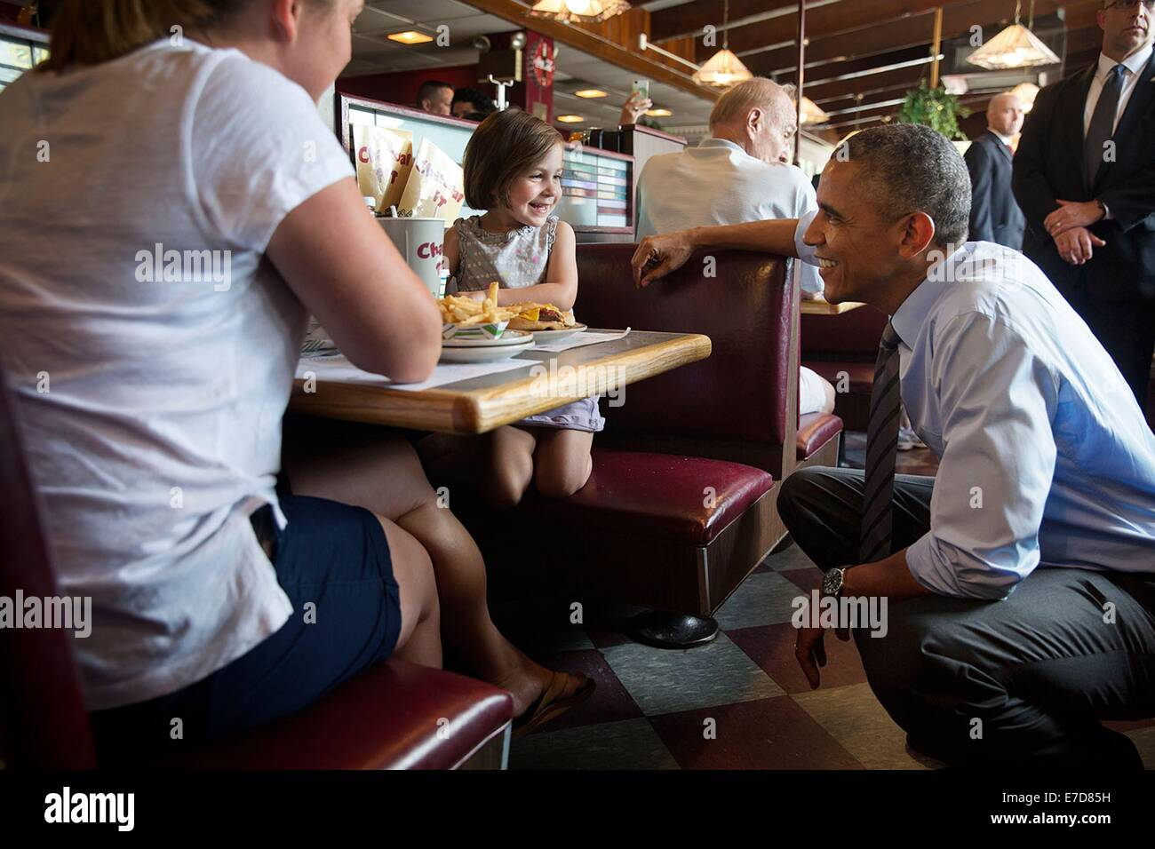US President Barack Obama talks with a little girl at the Charcoal Pit restaurant July 17, 2014 in Wilmington, Delaware. Stock Photo