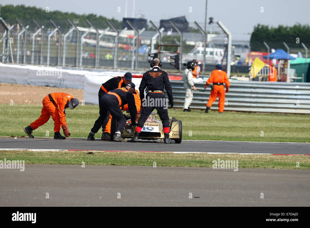 A classic Formula 3 car crashes and rolls over during a race for historic racing cars at the Silverstone Classic - Stock Image