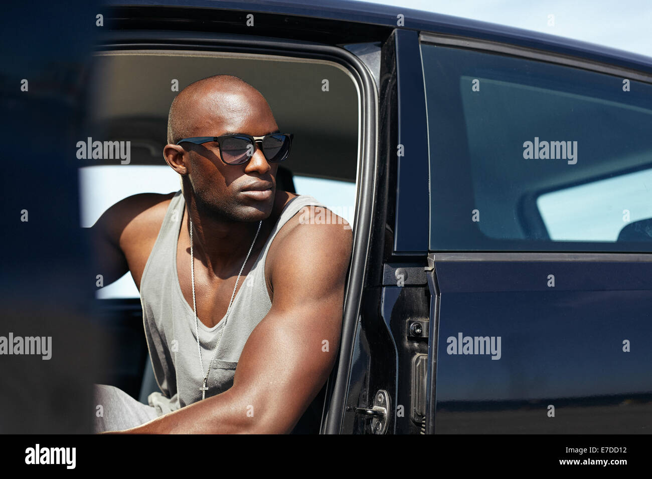 Image of young African man sitting in car looking away. Stylish Afro-American model sitting in car. - Stock Image
