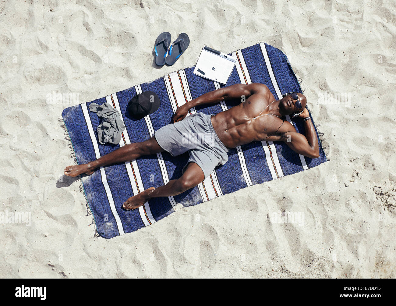 Top view of muscular young man sunbathing on beach. African guy wearing sunglasses and listening to music on headphones - Stock Image
