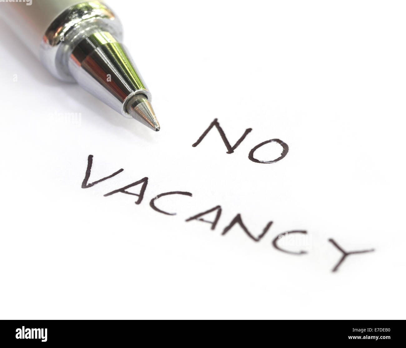 No vacancy written on a white paper with pen - Stock Image