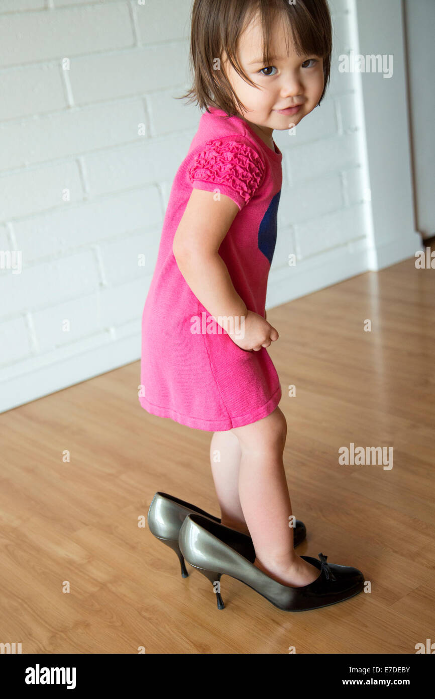 Baby girl in her mother's shoes - Stock Image