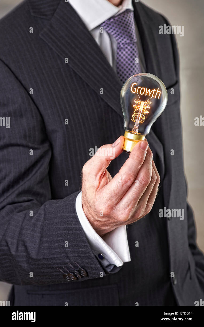 Businessman holding a lit lightbulb concept with the word Growth. - Stock Image