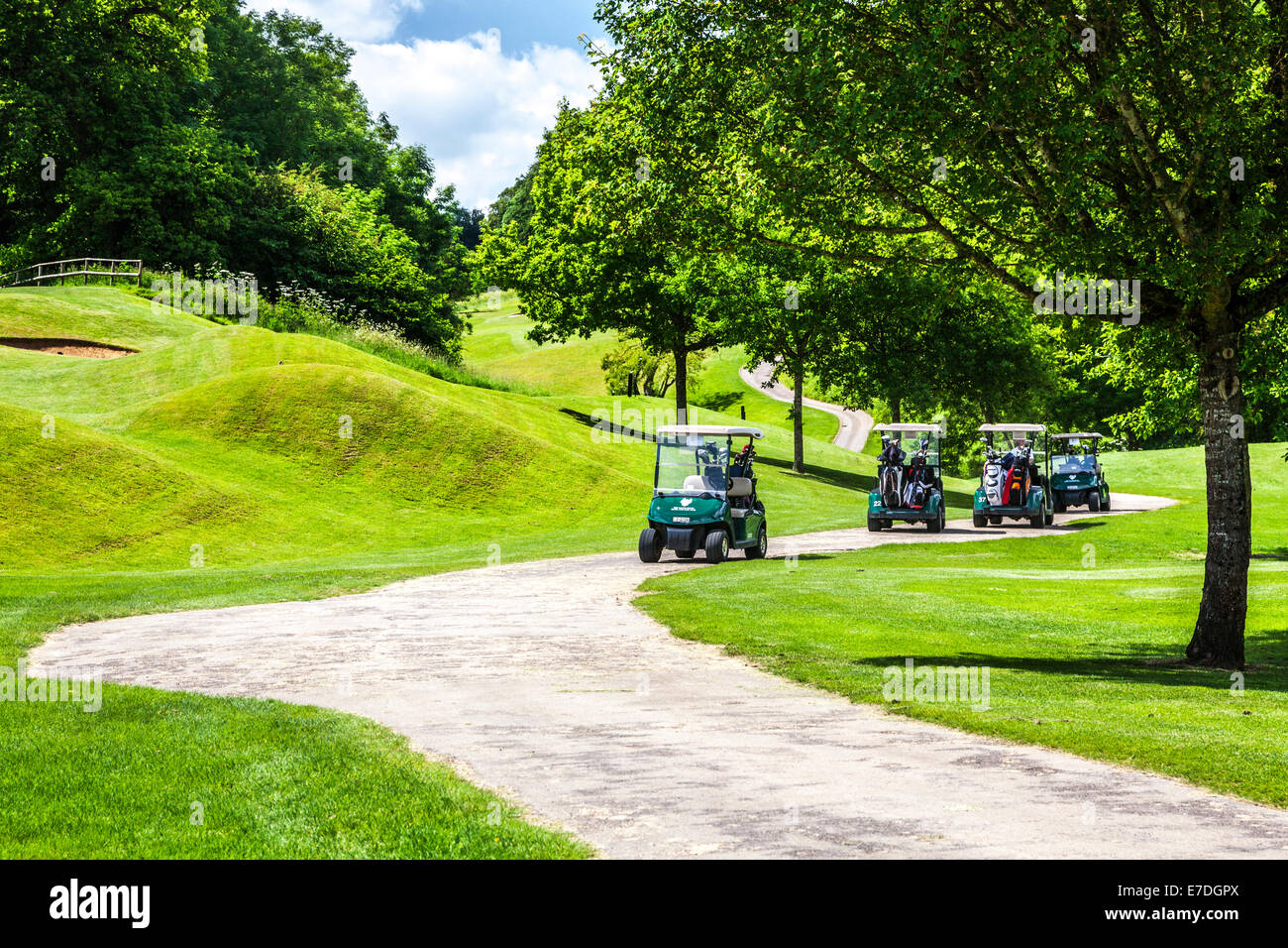 Four electric golf buggies by some bunkers on a golf course. - Stock Image