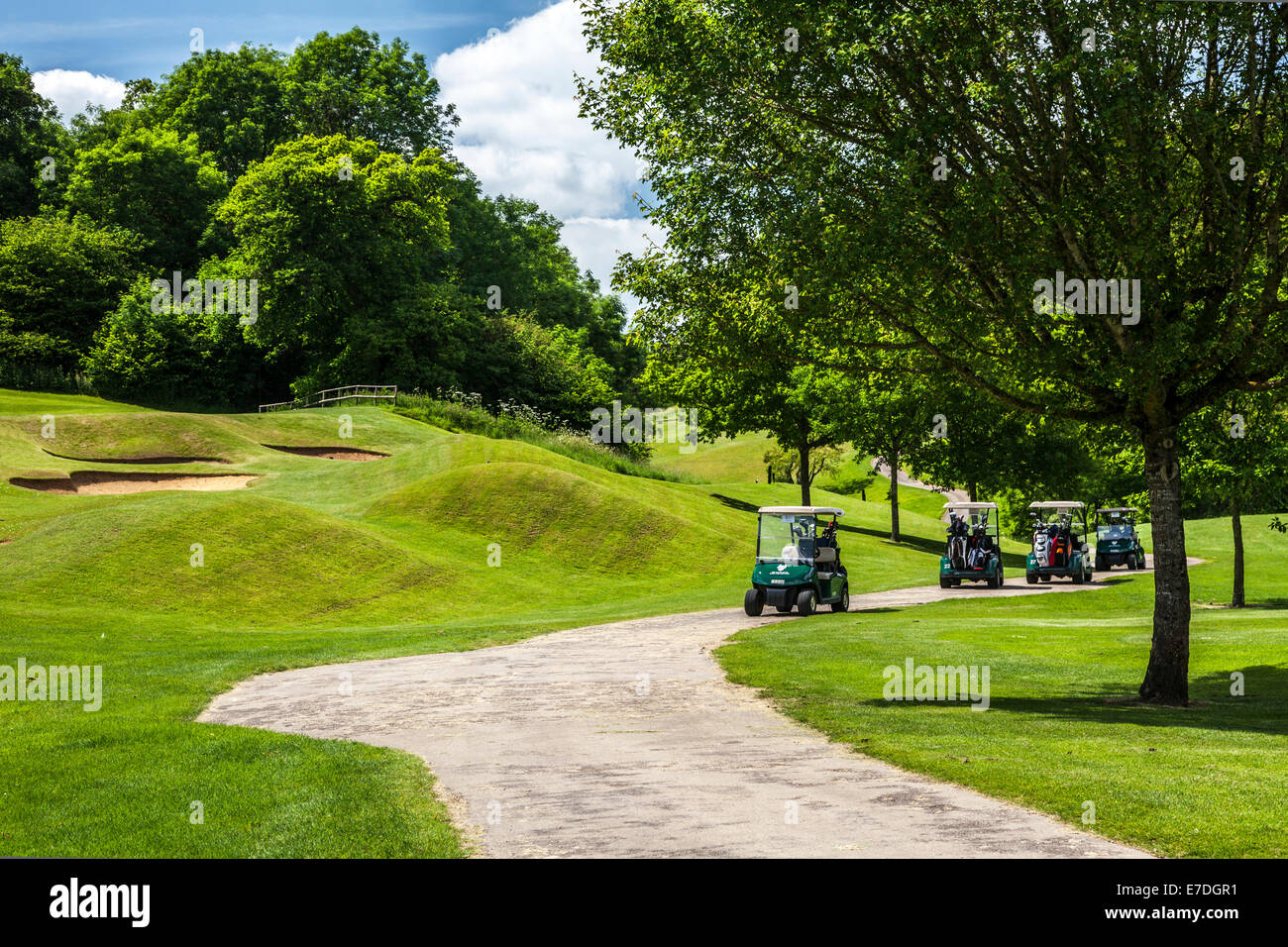 Four electric golf buggies or carts by some bunkers on a golf course. - Stock Image