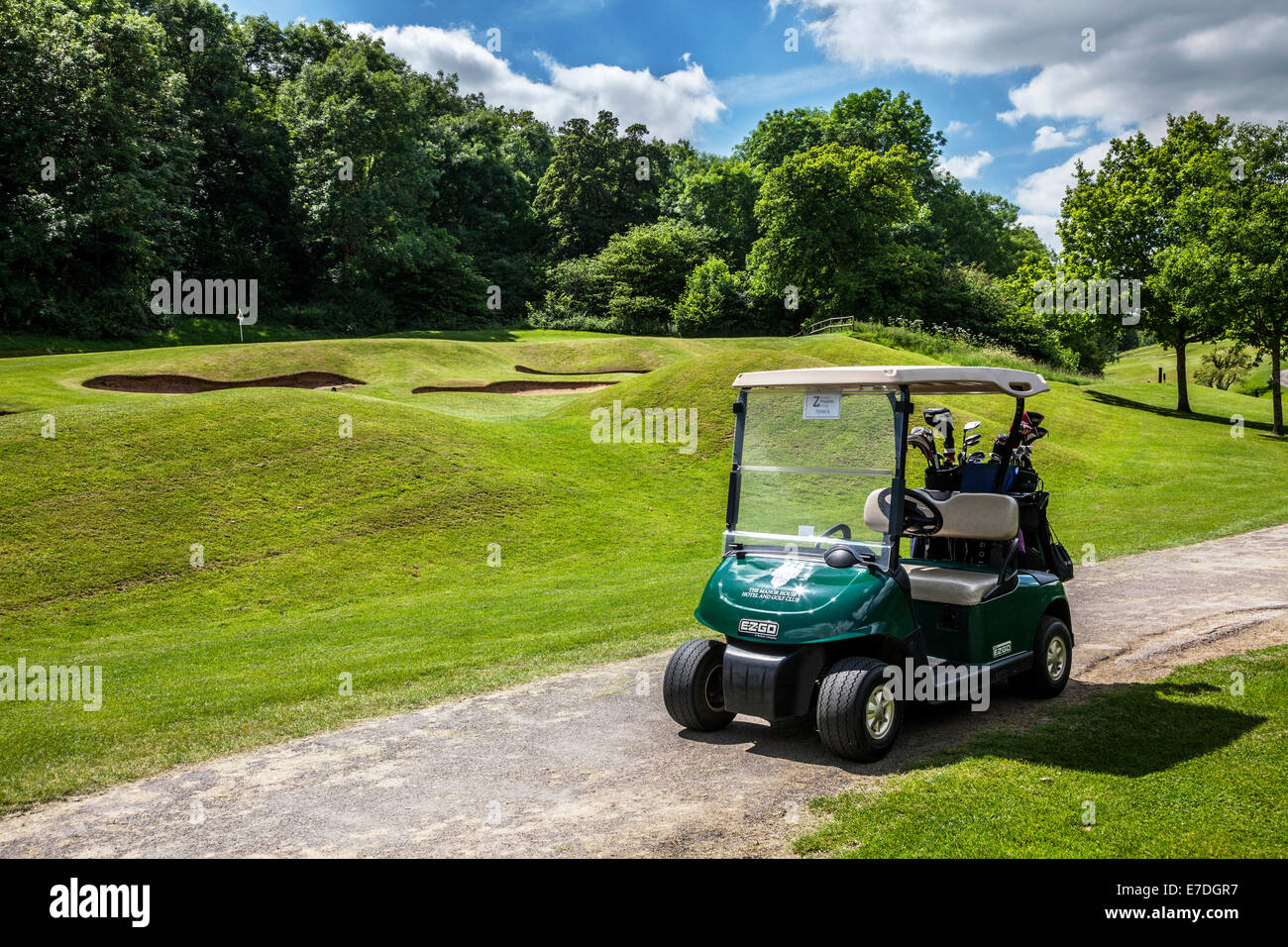 Bunkers by a putting green with flagstick and hole and an electric buggy or cart on a typical golf course. - Stock Image