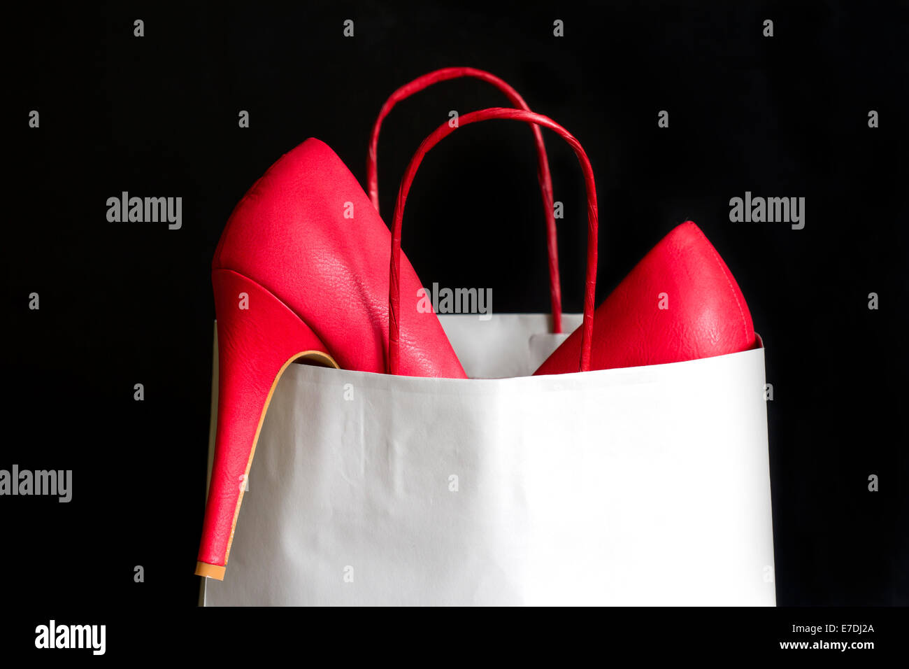 High heels red shoes in shopping bag against black - Stock Image