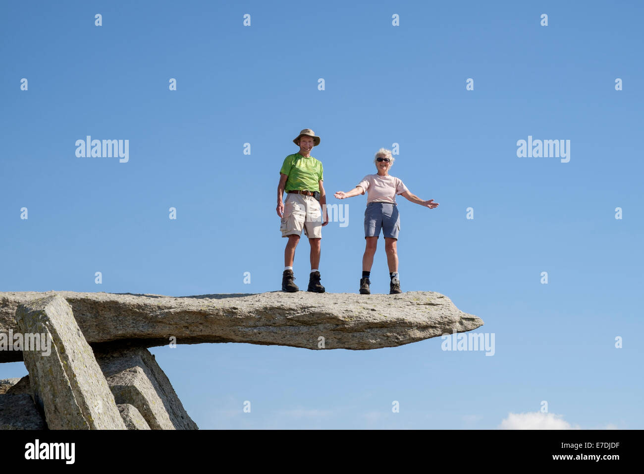 Two happy senior people with a sense of achievement living life to the full standing on cantilever rock on Glyder - Stock Image