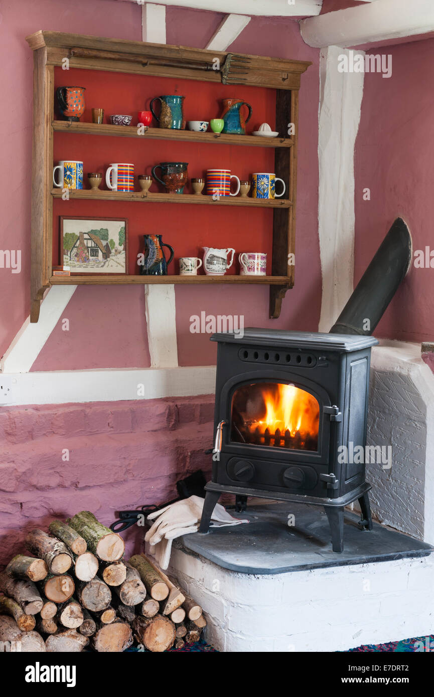 A cottage interior with a wood-burning stove installed in the sittingroom - Stock Image