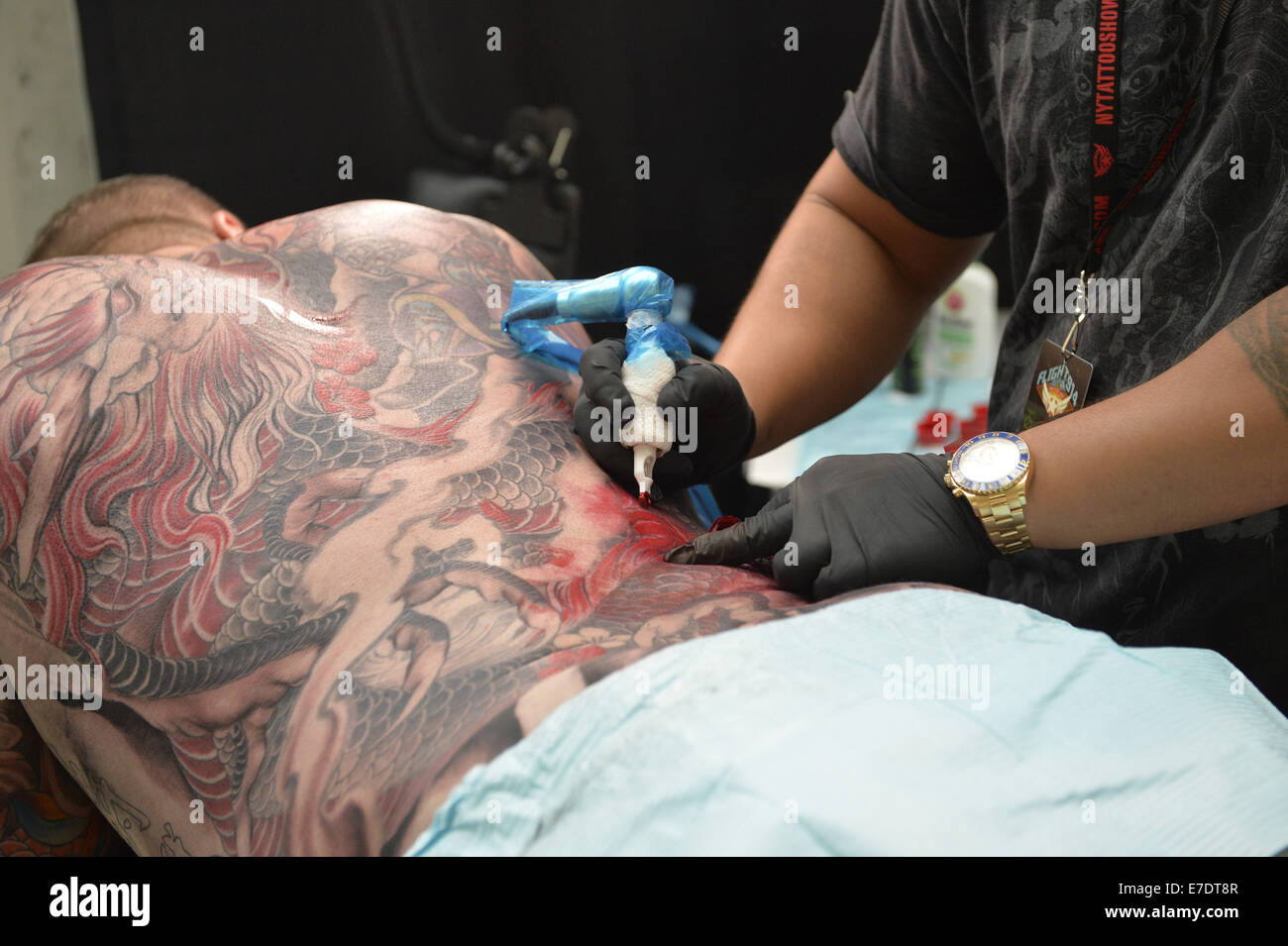 Garden City, New York, USA. 14th Sep, 2014. Tattoo artist MASTER MIKE, from Cambodia, tattoos the back of a man - Stock Image