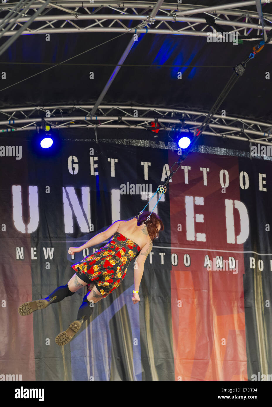 Garden City, New York, USA. 14th Sep, 2014. Young woman with tattoos is suspended from two ropes with hooks pierced - Stock Image