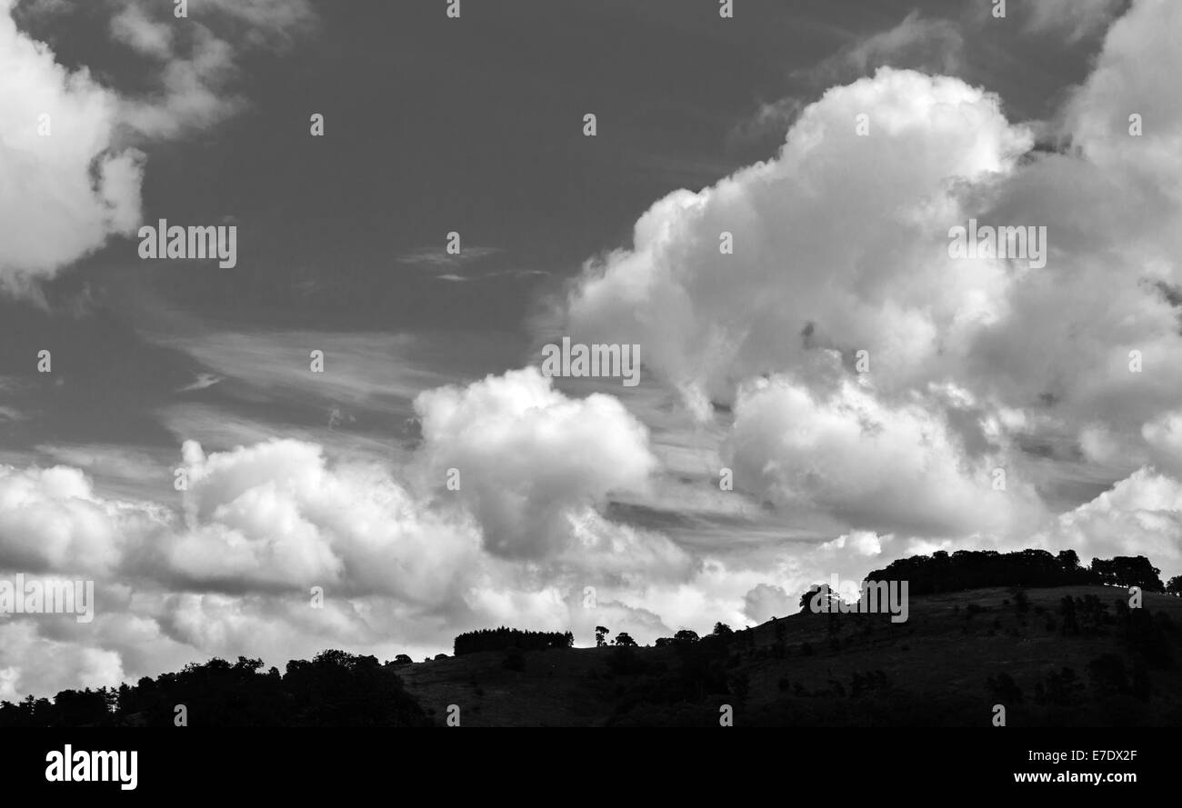 Cumulus clouds in summer above a silhouetted skyline in Wales, UK - Stock Image