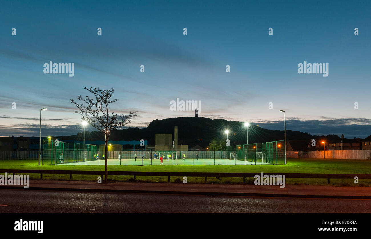 Newtownards, County Down, Northern Ireland. A floodlit football game taking place on astroturf. Scrabo Tower is - Stock Image