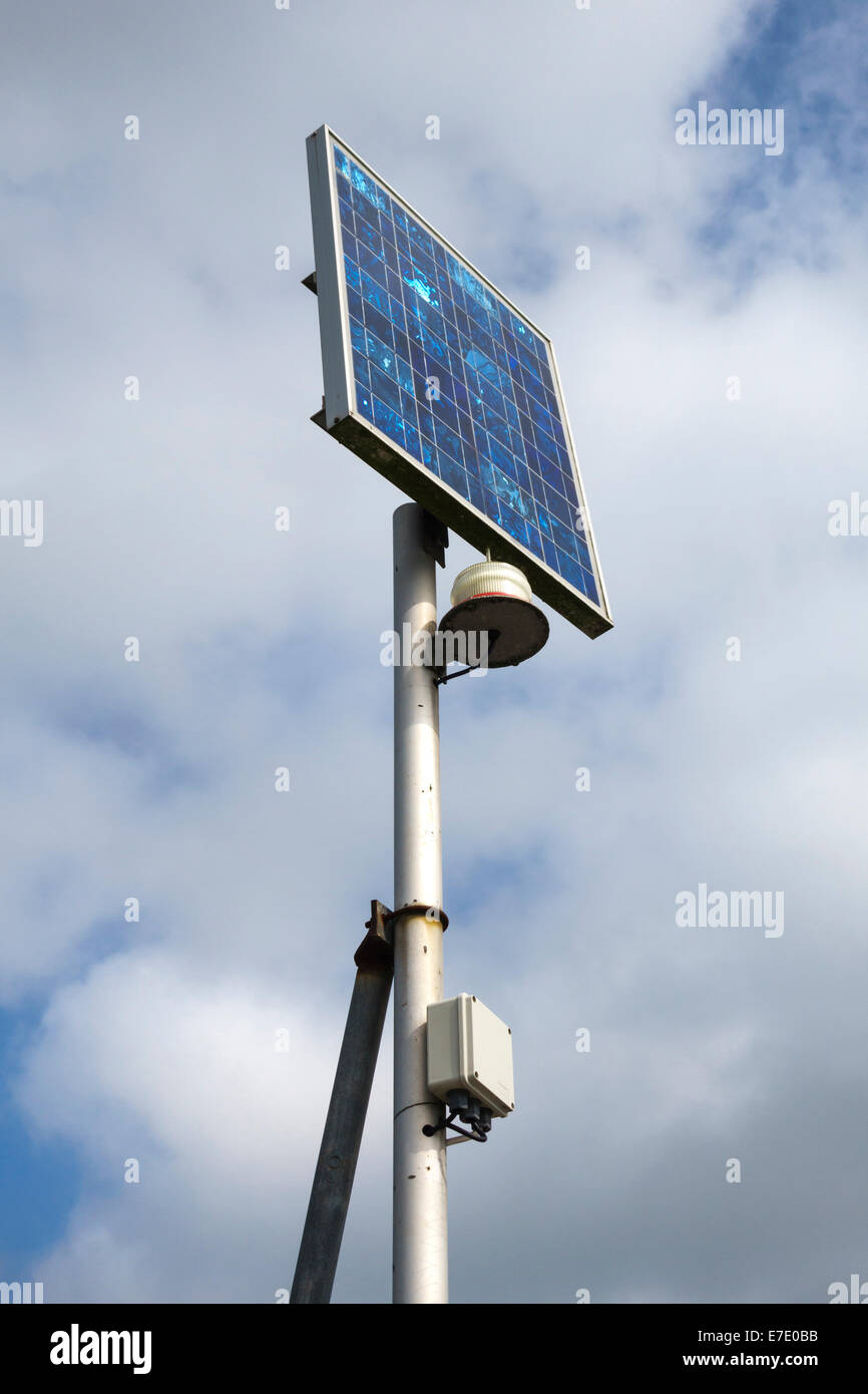 Small solar panel powering a navigation light in a marina, UK - Stock Image
