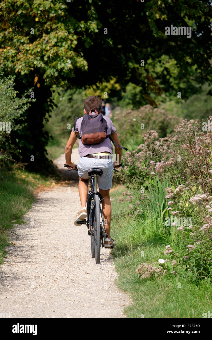 A young male cyclist wearing shorts and T shirt  carrying a rucksack on his back riding along a canal towpath on - Stock Image