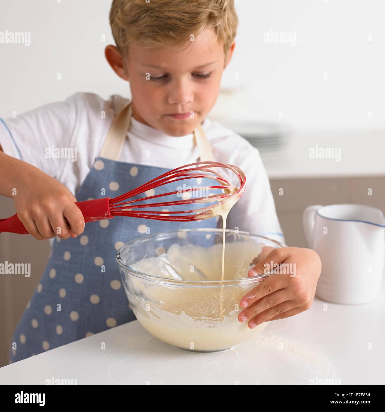 boy whisking batter to make pancakes Stock Photo