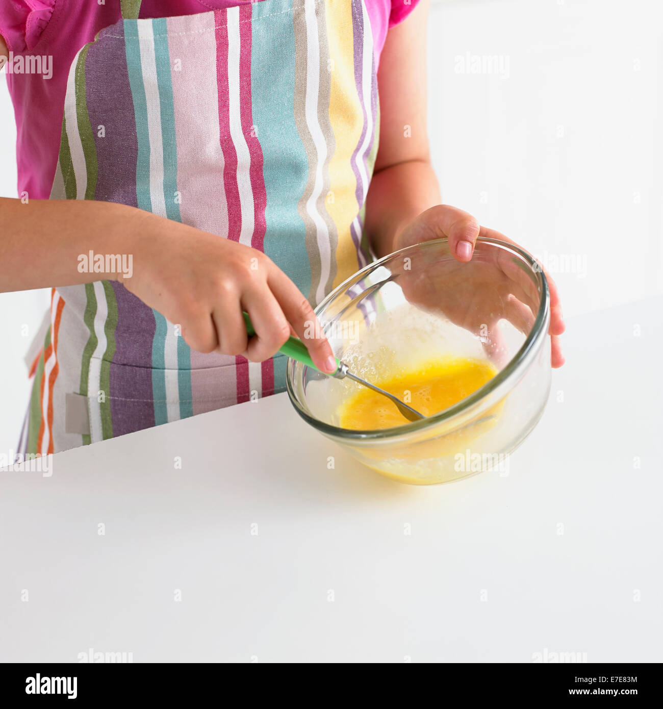 Girl whisking eggs in a bowl with a fork - Stock Image