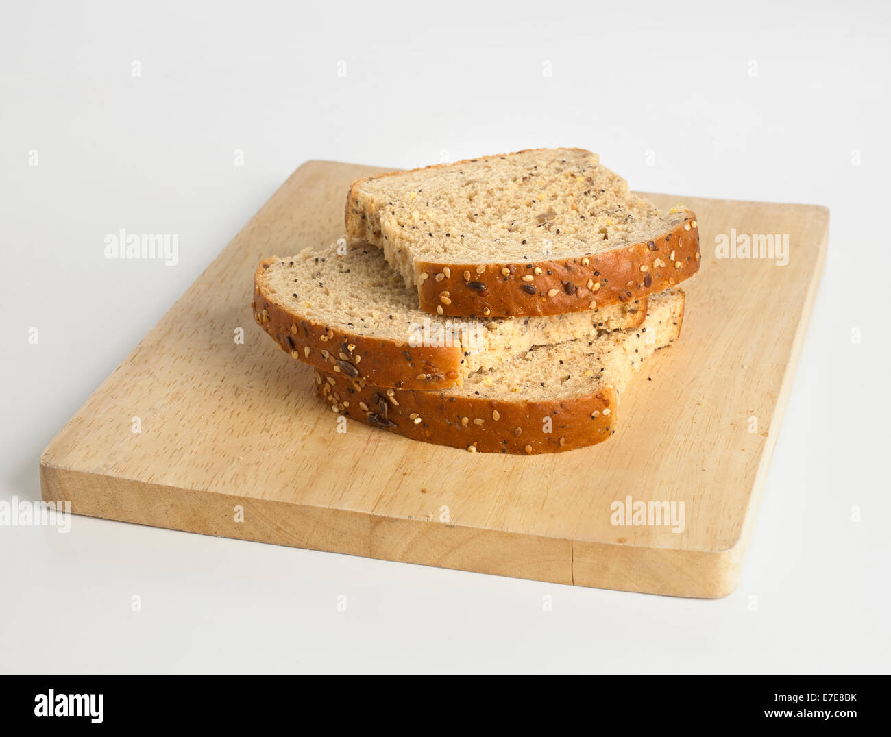 Three slices of seeded bread on breadboard - Stock Image