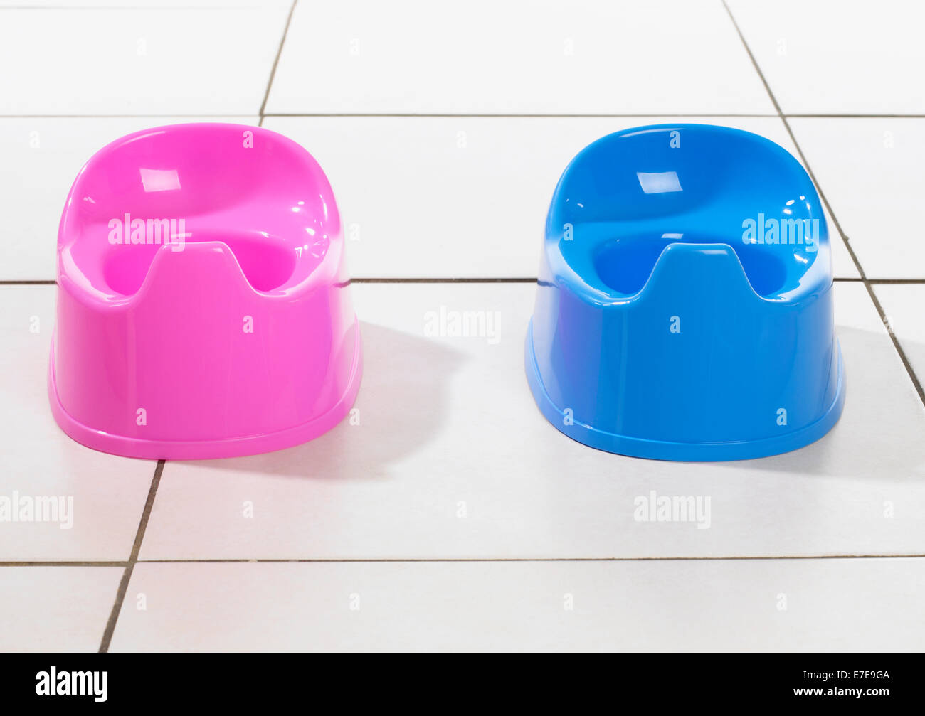 Plastic potties for girls and boys in pink and blue - Stock Image