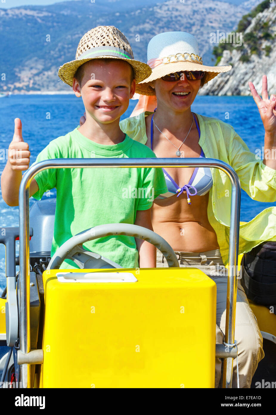 Mother with her son in a motorboat on sea promenade. - Stock Image
