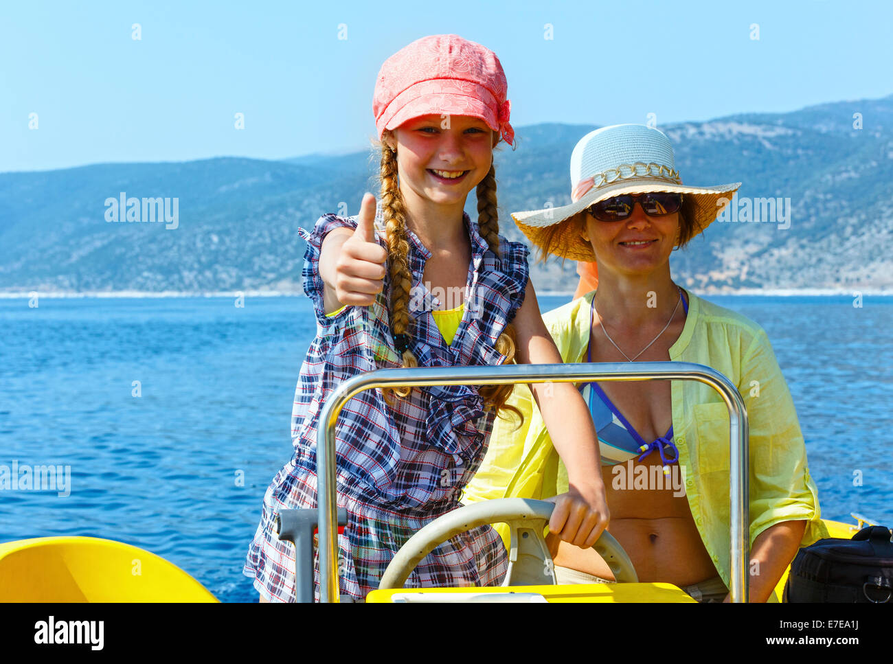 Mother with her daughter in a motorboat on sea promenade. Stock Photo