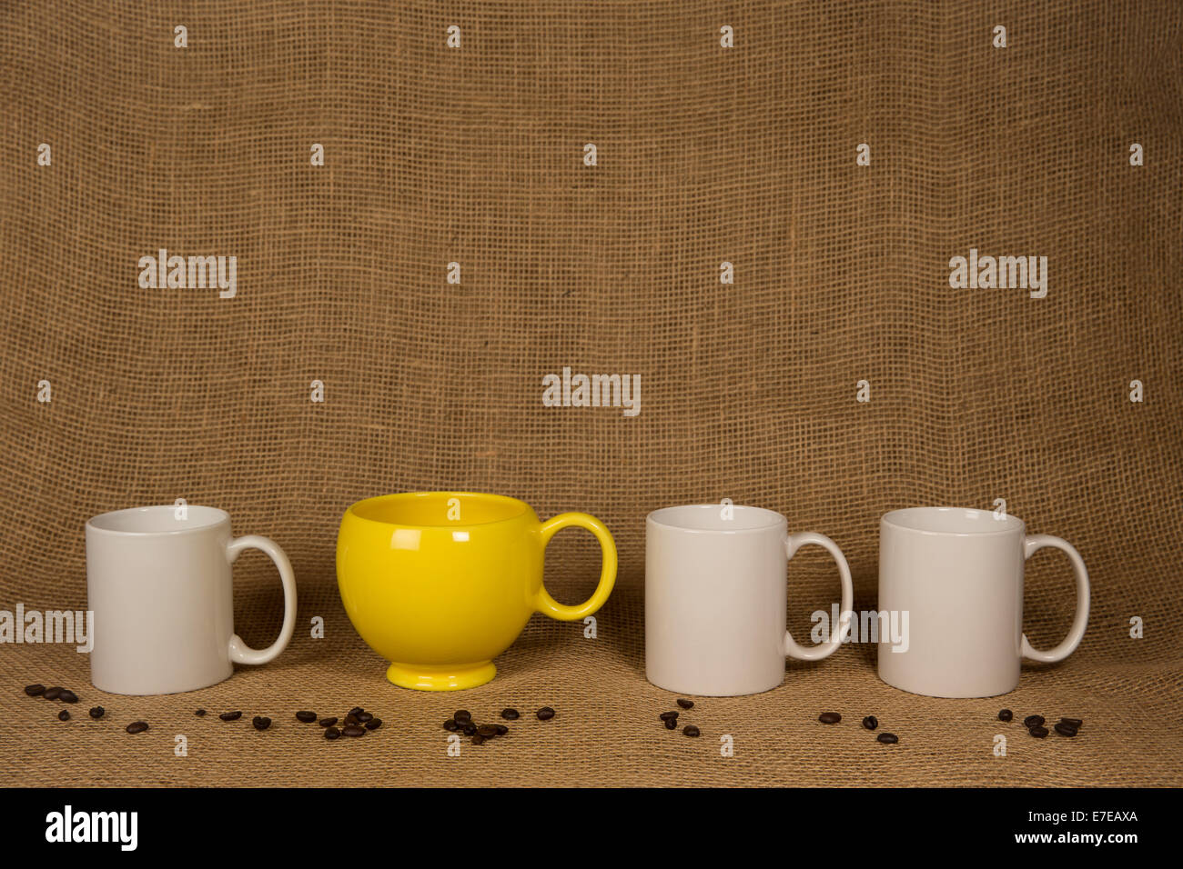 Coffee Mug Background.  One unique yellow mug, three white ones, coffee beans on burlap.  Copy space on mugs and - Stock Image