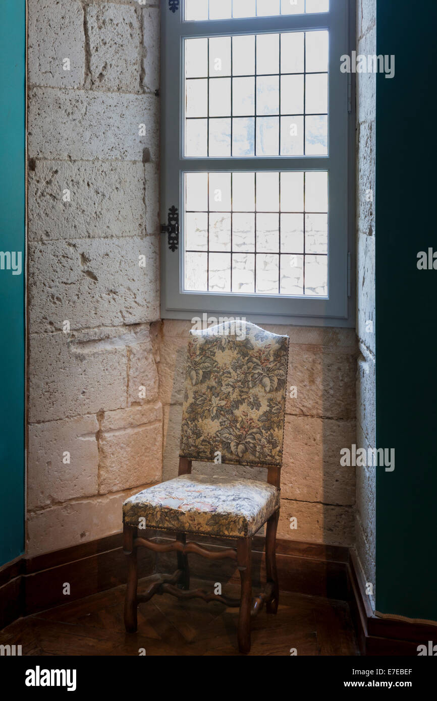 17c upholstered chair under window in the Chateau de Monbazillac France. - Stock Image