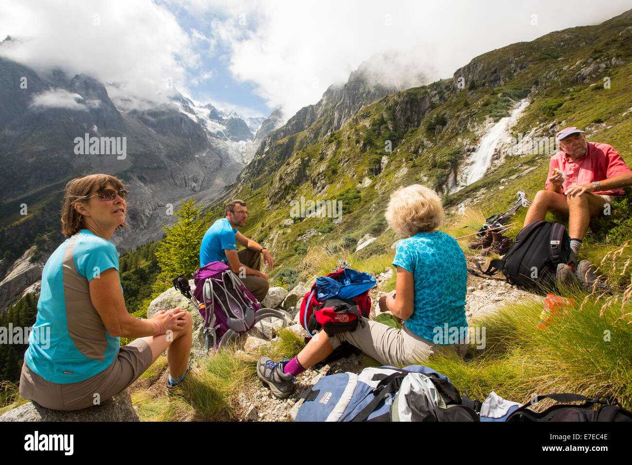 Walkers doing the Tour du Mont blanc ascend towards the Cabanne D'Orny infront of the rapidly receding Glacier de Stock Photo