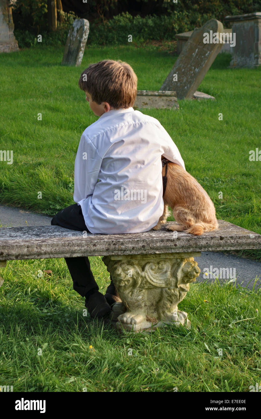 Boy holding a puppy, sitting in a churchyard, UK - Stock Image