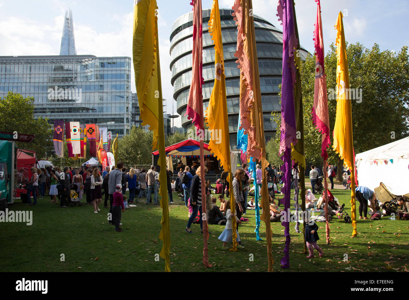 People gathering to hang out, listen to bands and other activities at the Blue Ribbon Village. Thames Festival London Stock Photo