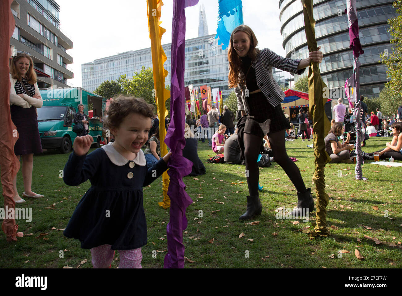 People gathering to hang out, listen to bands and other activities at the Blue Ribbon Village. Thames Festival London - Stock Image