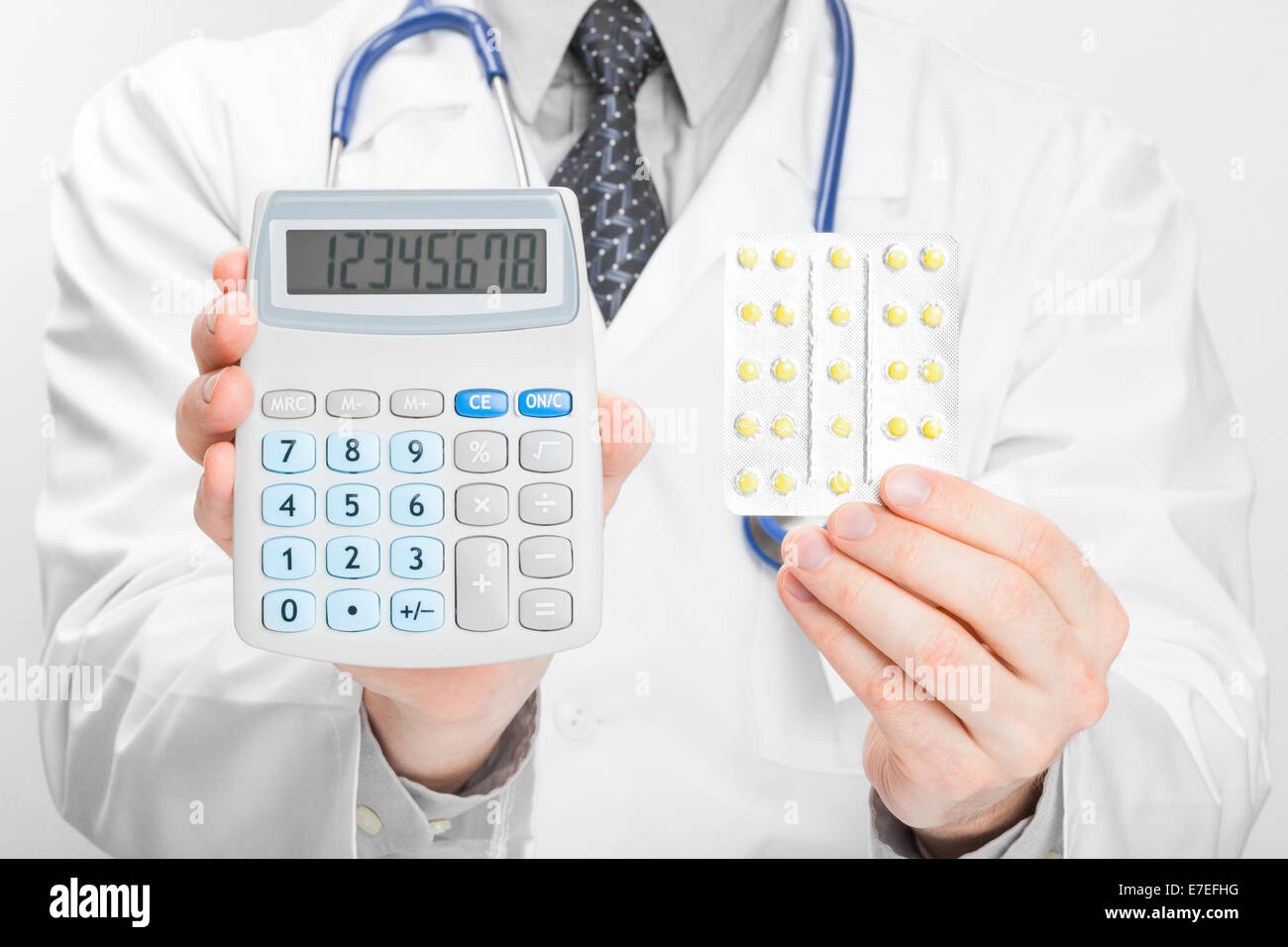 Doctor holdling calculator and pills in his hands - heath care concept Stock Photo