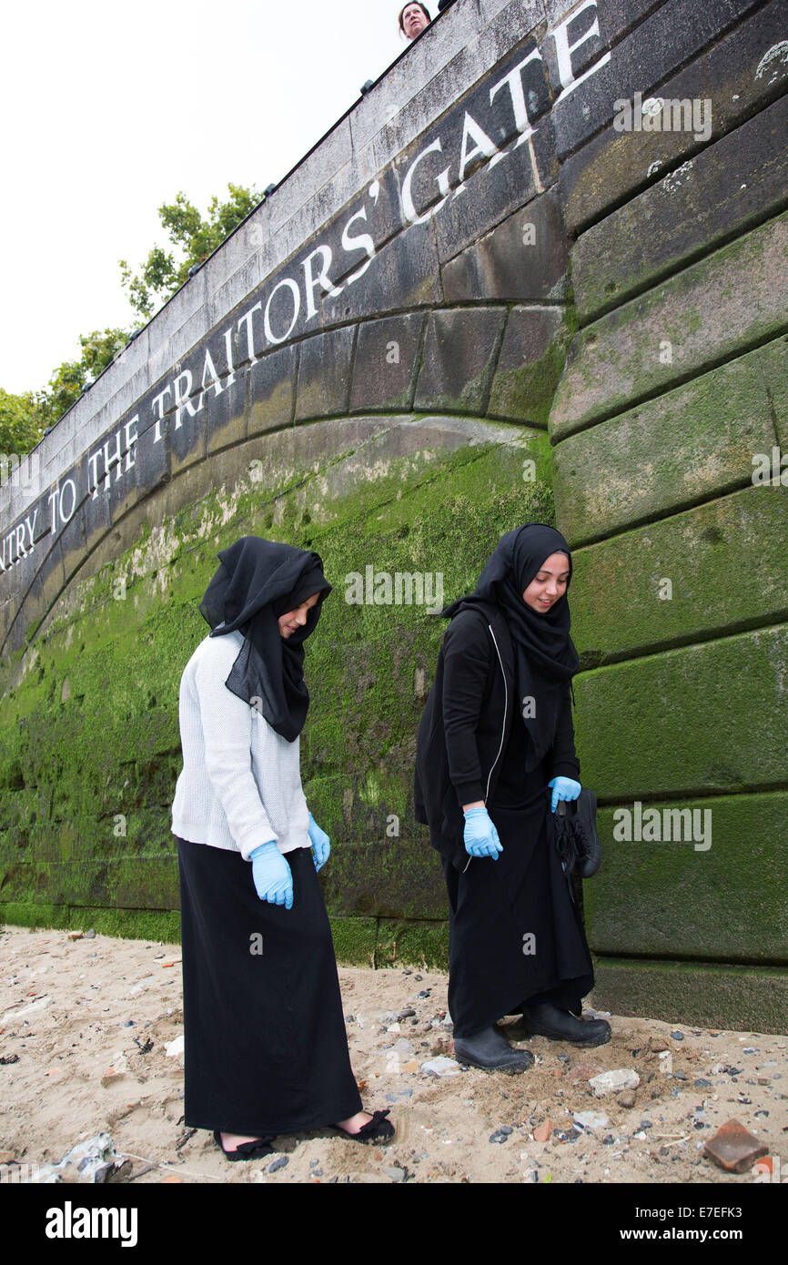 Muslim family looking for artifacts at Traitors Gate at low tide on Tower Beach, which is only open once per year. - Stock Image