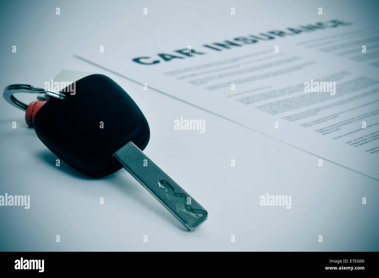 closeup of a car key and a car insurance policy - Stock Image