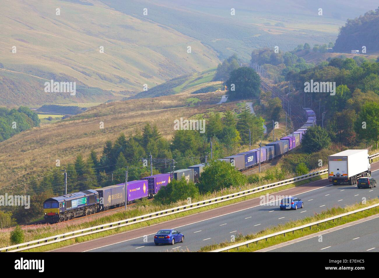 Direcr Rail Services (DRS) diesel freight train passing the M6 motorway in the River Lune Valley. Howgills, Cumbria, - Stock Image