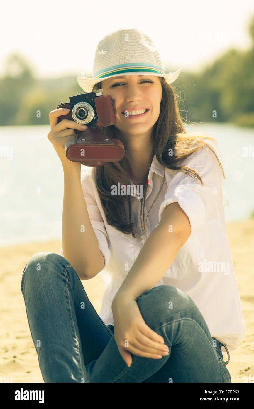 Young woman posing with old film camera. Caucasian hipster girl in hat spend funny time at the beach. Warm color - Stock Image