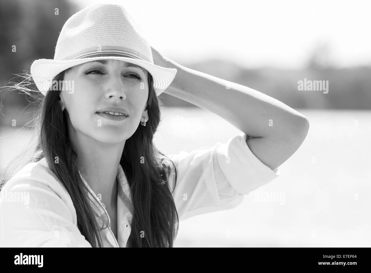 Caucasian girl in hat at summer midday near the river or lake. Black and white image Stock Photo