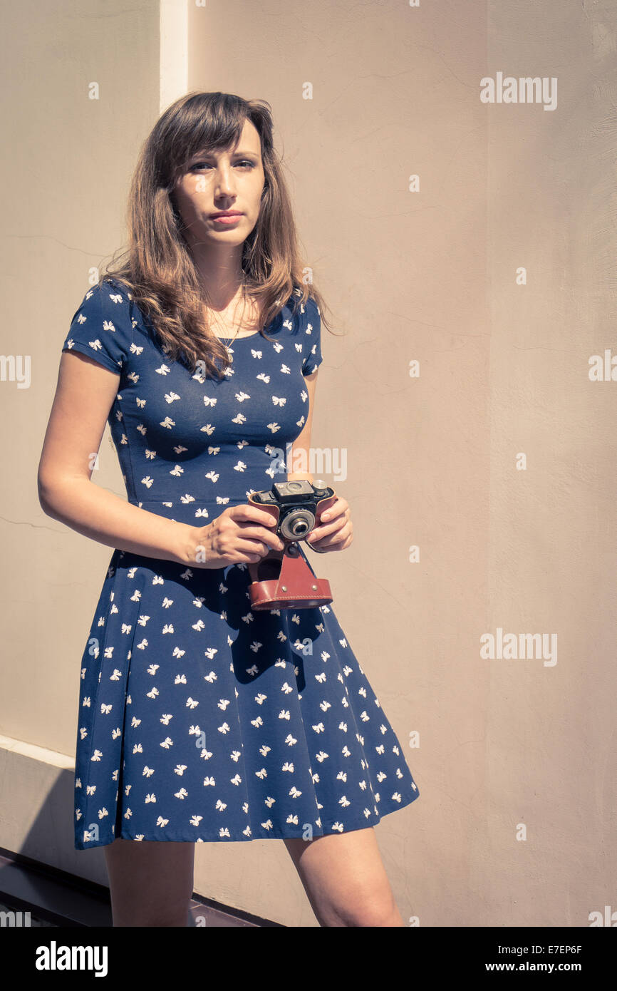 Young hipster girl walking with old film camera - Stock Image