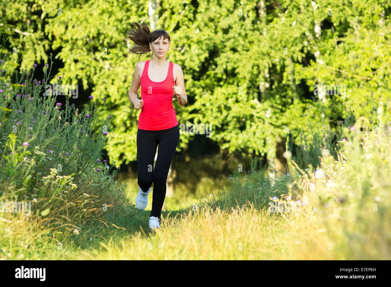 Young woman dressed in sportwear jogging at summer park - Stock Image