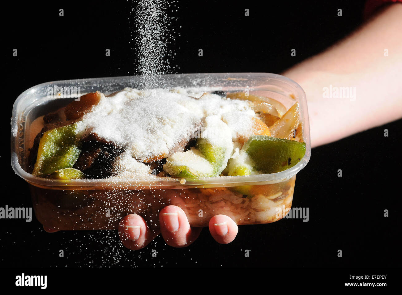 A woman pours salt on an unhealthy takeaway meal. - Stock Image