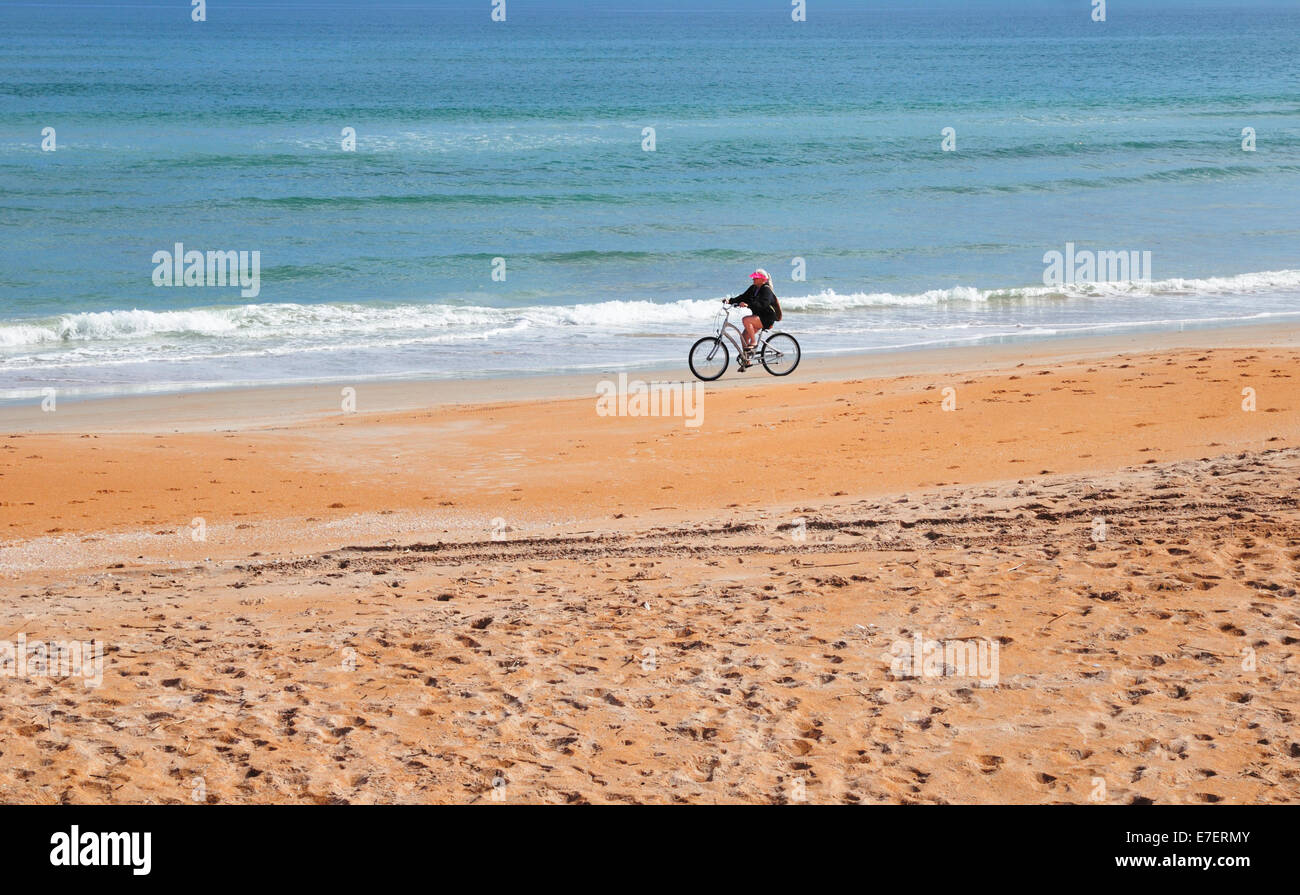 Bicyclist enjoys traveling on the hard packed sand of Ormond Beach, Florida - Stock Image