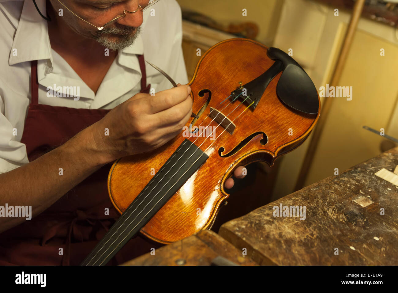 Violin maker making adjustments to the sound post with special tool i - Stock Image