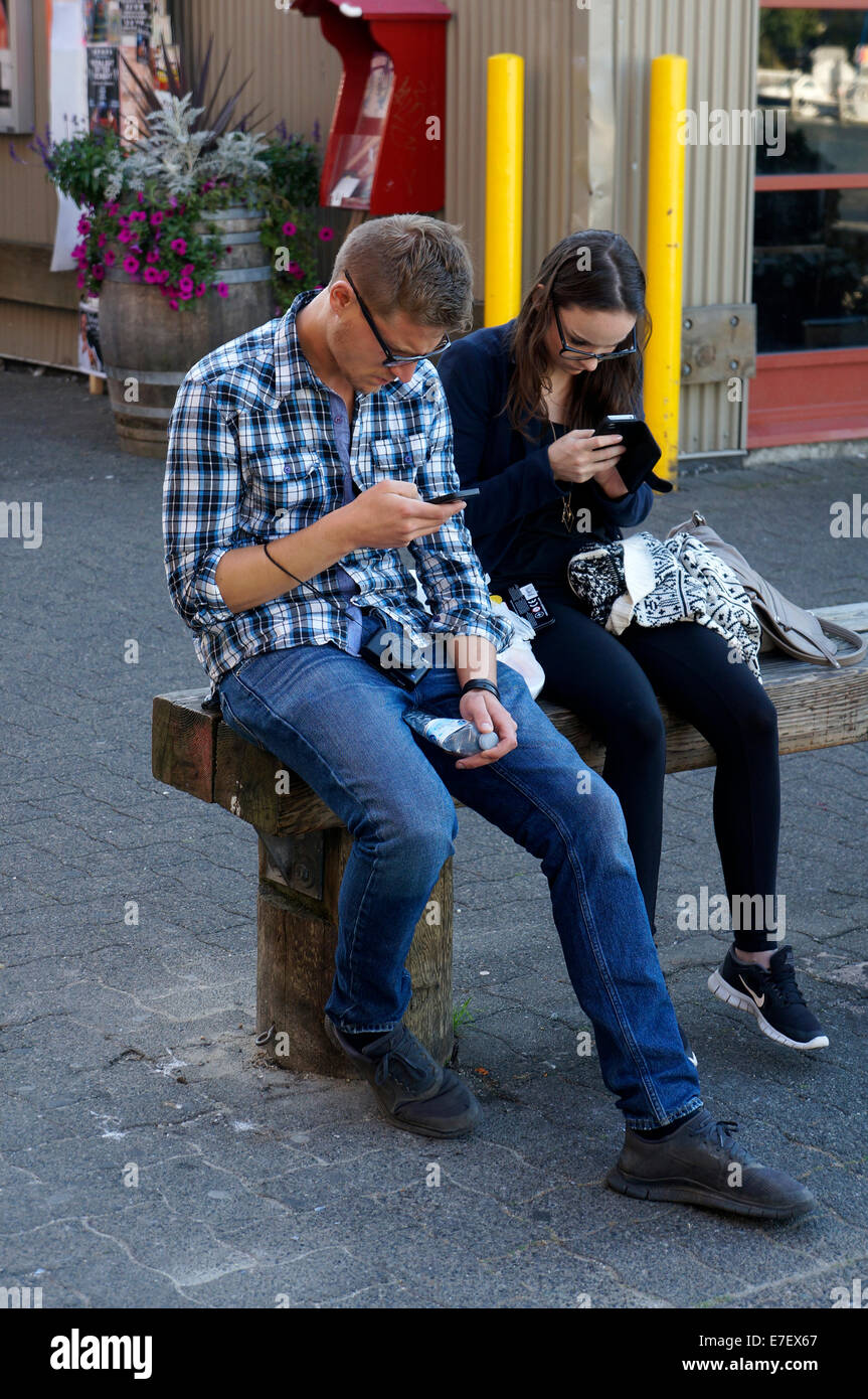 Young man and woman sitting on bench using their cell phones, Vancouver, BC, Canada - Stock Image