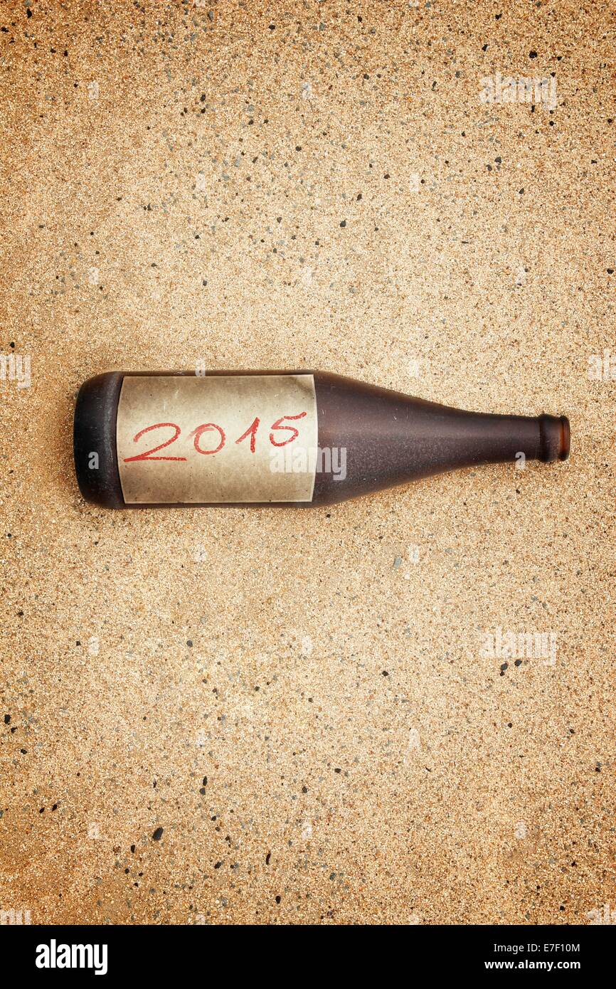 Vintage version of washed out bottle with 2015  label on gravel beach. - Stock Image