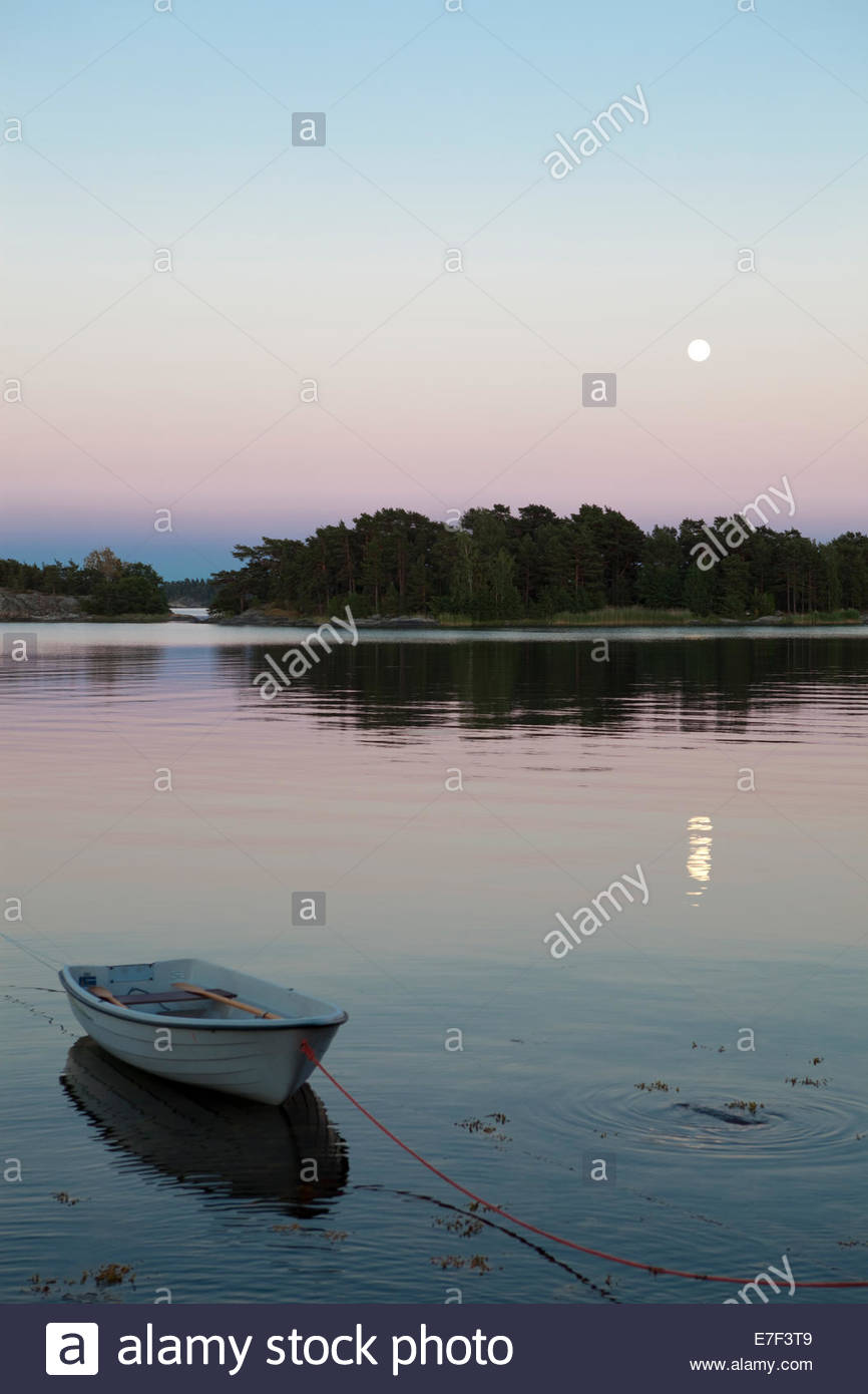 Moonshine over Baltic Sea, a boat by the shore in the archipelago of Turku - Stock Image
