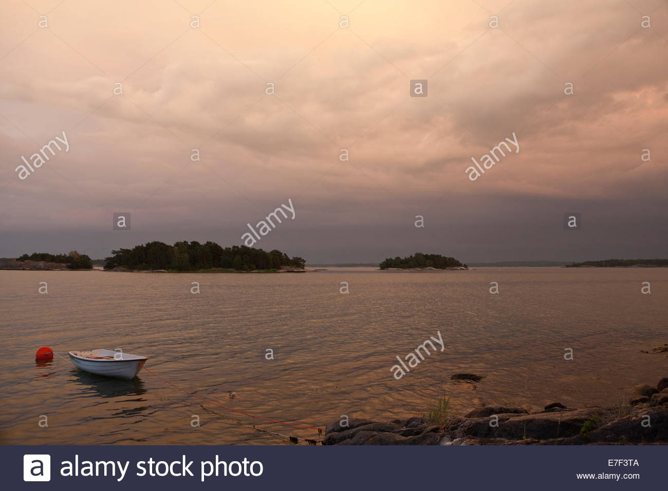 A rowboat by the sea in the summer evening - Stock Image