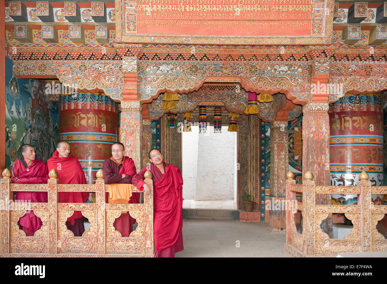 Four monks in red robes, ornate wooden wall, Buddhist Tango Goemba Monastery near Thimphu, Kingdom of Bhutan - Stock Image