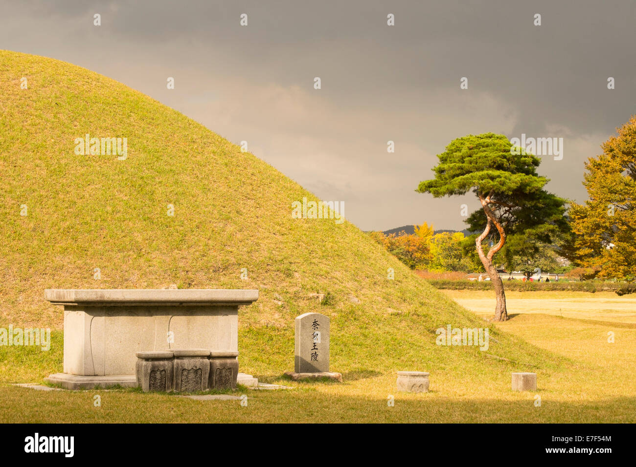 Tumulus grave in front of a mystically darkened sky, Gyeoungju, South Korea - Stock Image