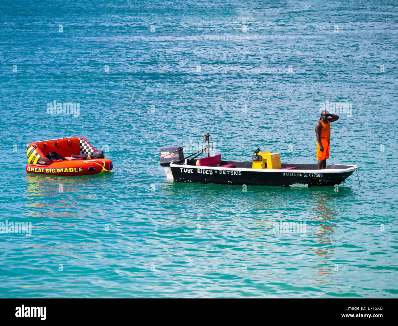 Man hiring out boats waits for customers, Rodney Bay, Saint Lucia, Windward Islands, Lesser Antilles - Stock Image